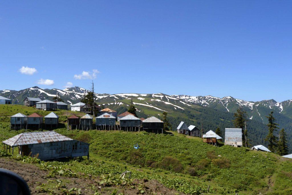 Domki lokalsów na tle ośnieżonych gór.